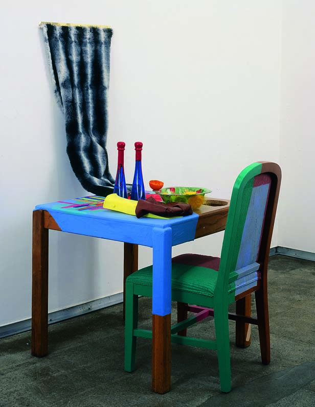 2003 wooden table, two blue glass bottles, flipper, painted shower curtain, acrylic paint, pink upholstered chair, fur on hinge, plastic bowl, plastic orange 58.5 x 53 x 30 in 148.6 x 134.6 x 76.2 cm